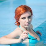 young adult woman in bikini leaning against pool wall