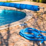 pool cover back and vaccum hose coiled