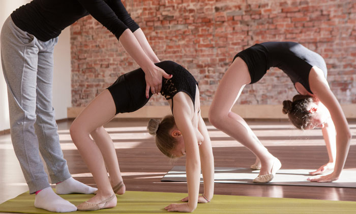 dance instructor positioning young girl dancers bodies
