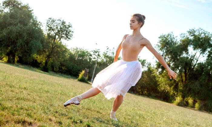 teen ballerina girl outside dancing in grass