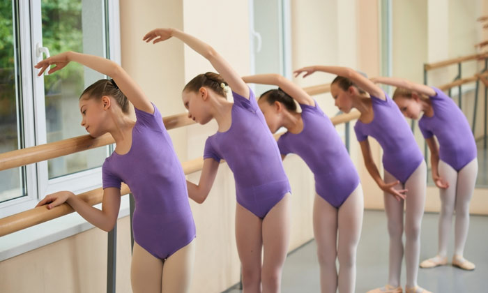 young ballerina girls bending over one side