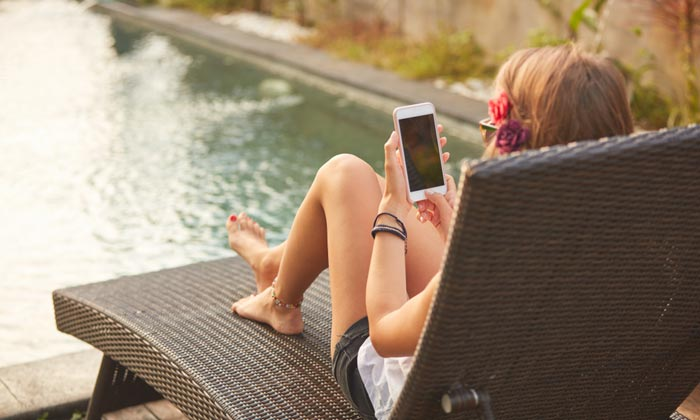 young woman on phone sitting beside pool