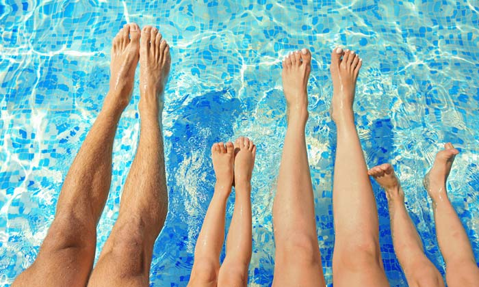 family legs feet outstretched over pool water