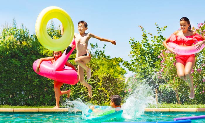 kids with pool tubes jumping into water