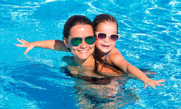 mother in pool with young daughter on back