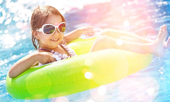 sunglass girl smiling as floating on pool water