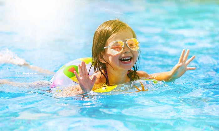 sunglass young girl floating in pool with tube