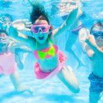 underwater goggle kids swimming happily