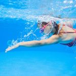 young girl swimming underwater with goggles