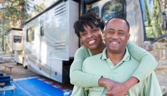 happy couple vacationing with trailer