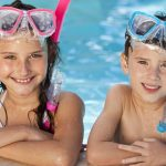 brother and sister with diving gear in pool