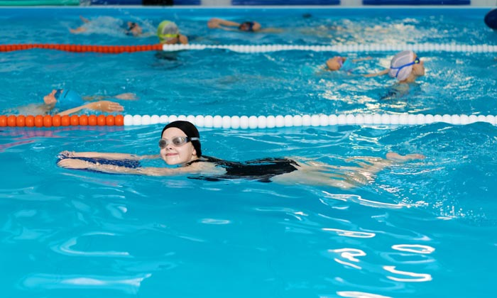 children learning how to swim with boards