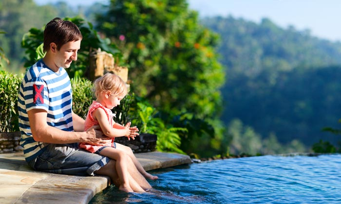 father holding young daughter with toes in pool