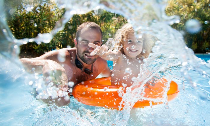 father with young son splashing camera in pool