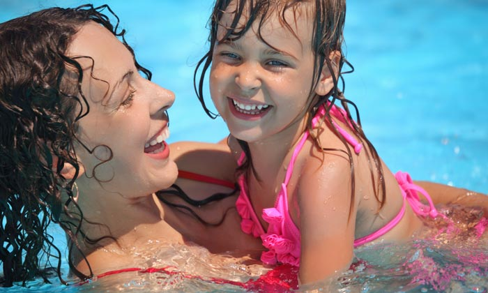 happy mother holding young daughter in pool