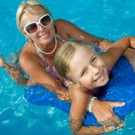 mother helping young daughter use kickboard in pool