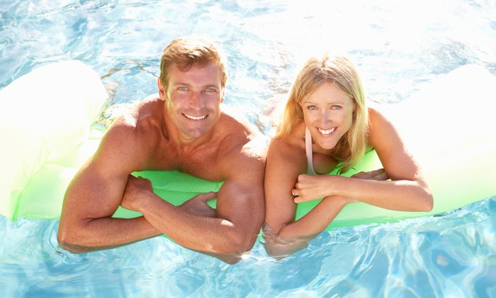 muscular dad with mom on pool float
