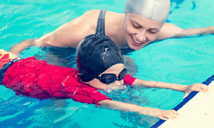 swim instructor helping young boy blow water bubbles