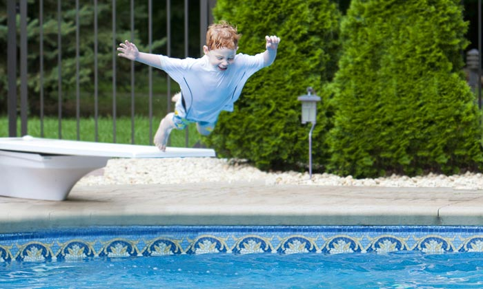 young boy about to bellyflop into pool