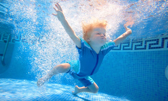 young boy making bubbles swimming underwater