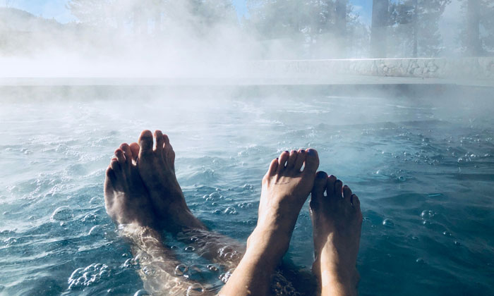 husband and wife feet relaxing in hot tub