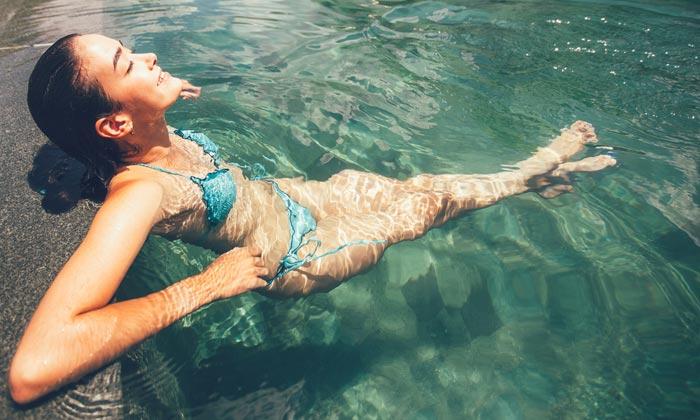 young adult woman wearing bikini enjoying pool water