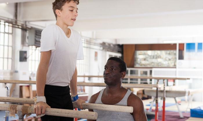 gymnastics teacher guiding young boy student