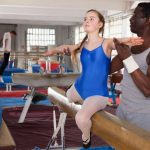 gymnastics teacher instructing young girl student
