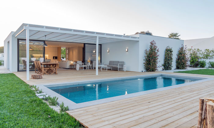 flat roofed contemporary home with backyard inground pool