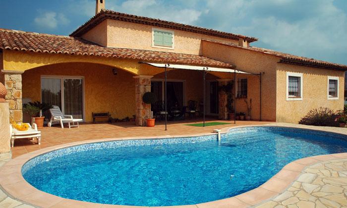 inground pool behind house in hot region